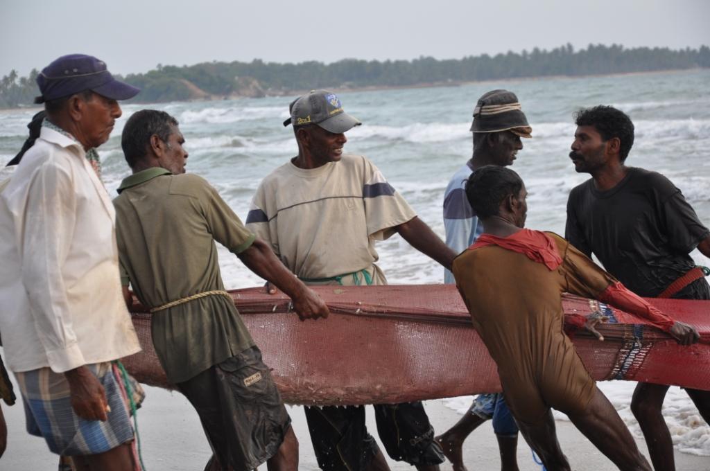 Fischer ziehen Netz an Land